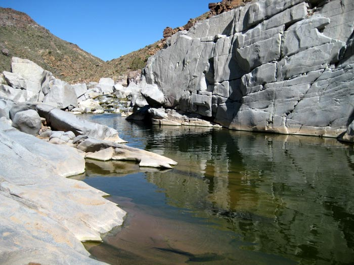 The solid granite bank of the Agua Fria River